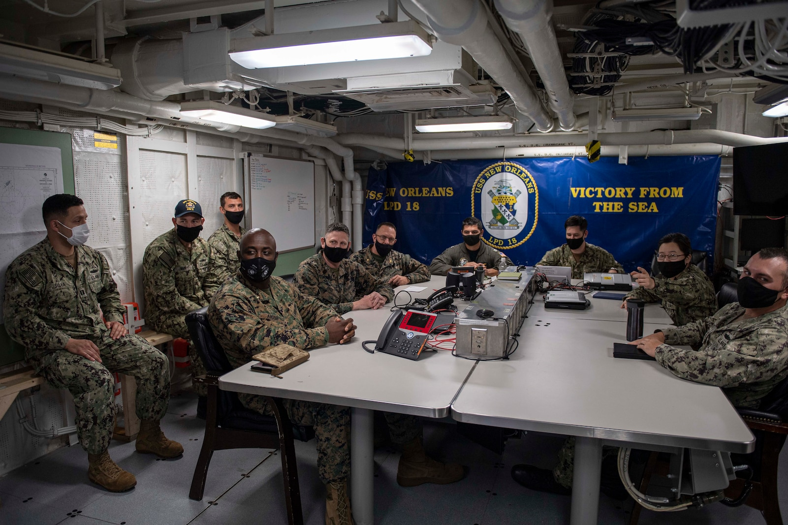 SASEBO, Japan (April 26, 2021) Staff of the 3D Marine Expeditionary Brigade (3D MEB), part of III Marine Expeditionary Force, and the USS New Orleans (LPD 18), part of Commander Task Force-76 (CTF-76), 7th Fleet, conduct a video teleconference onboard ship April 26 as part of Fleet Synthetic Training-Joint (FST-J). Pictured from 3D MEB are Maj. Jeff Adusei, Future Operations planner; Master Sgt. Justin Byrd, Fires and Effects Chief; and Maj. Brian Taylor, Air Planner. Teamwork between 3D MEB and CTF-76 greatly expands the network of resources that can be brought to bear on any given problem in any given location. New Orleans, part of the America Amphibious Ready Group, along with the 3D Marine Expeditionary Brigade, was operating in the U.S. 7th Fleet area of responsibility to enhance interoperability with allies and partners and serve as a ready response force to defend peace and stability in the Indo-Pacific region. (U.S. Navy photos by Mass Communication Specialist 2nd Class Kelby Sanders)