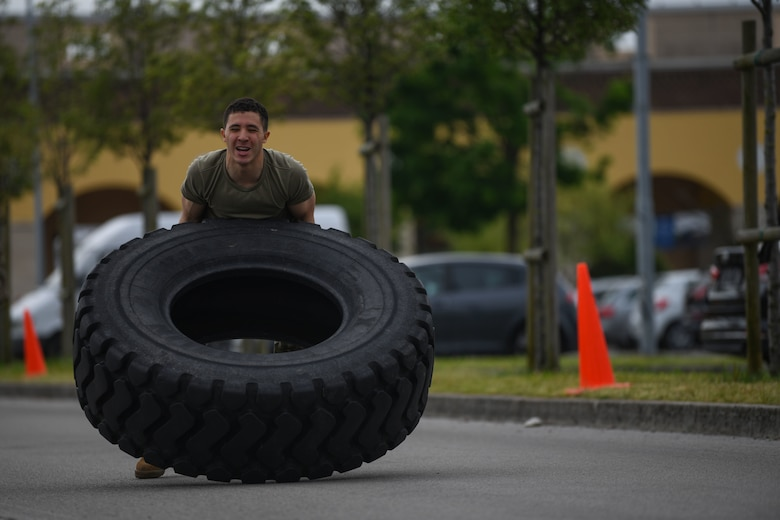Airman Wesley J. Harding-Brown, 31st Security Forces Squadron (SFS) member, flips a tire during Police Week at Aviano Air Base, Italy, May 11, 2021. Airmen from the 31st SFS and 31st Civil Engineer Squadron competed in an obstacle course. The course consisted of a hose drag, litter carry, body drag, tire flips, Keiser FORCE Machine, sprints, M4 carbine assembly and disassembly, and a Humvee team push. (U.S. Air Force photo by Senior Airman Ericka A. Woolever)
