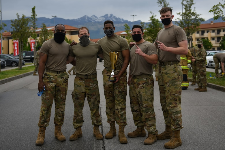 """Airmen from the 31st Civil Engineer Squadron (CES) won first place in a """"Guns and Hoses"""" competition during Police Week at Aviano Air Base, Italy, May 11, 2021. The 31st CES team won with the best time of 13 minutes, 1 second. The competition consisted of a hose drag, litter carry, body drag, tire flips, Keiser FORCE Machine, sprints, M4 carbine assembly and disassembly, and a Humvee team push. (U.S. Air Force photo by Senior Airman Ericka A. Woolever)"""