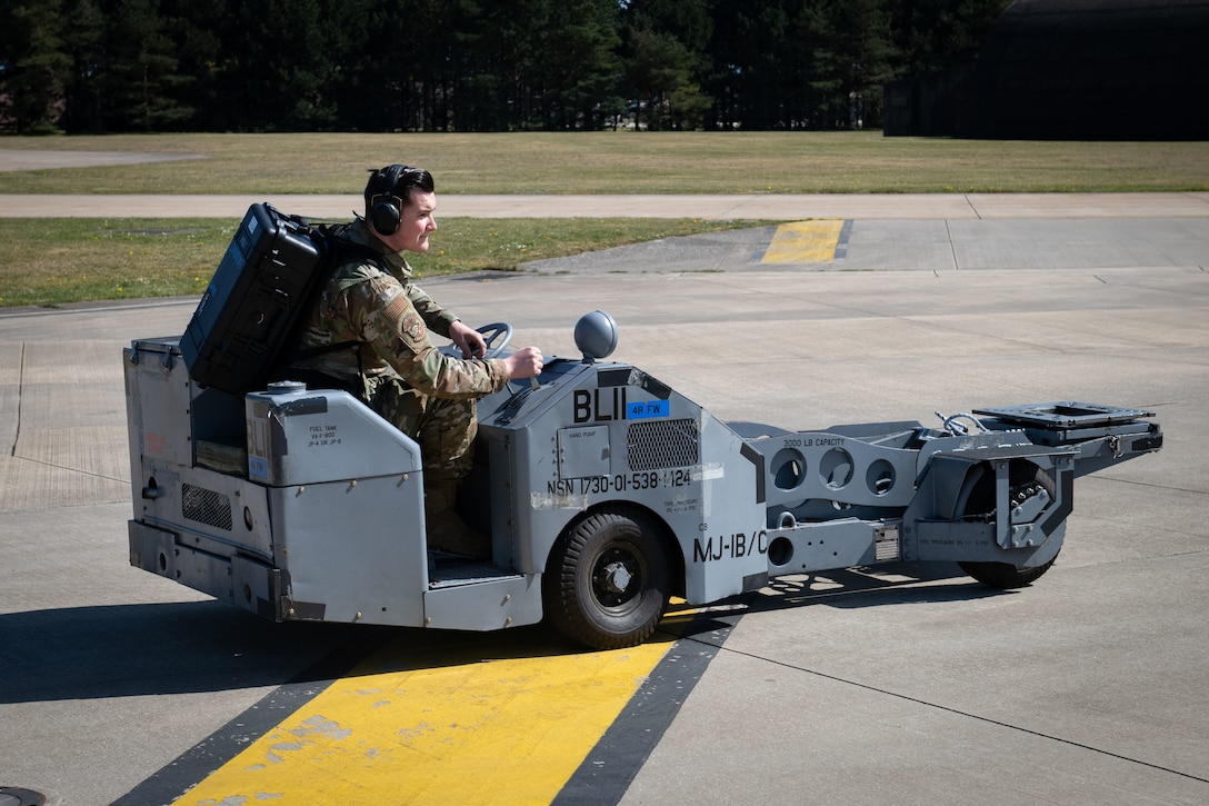 U.S. Air Force Senior Airman Shawn McIntosh, a weapons load crew member with the 492nd Aircraft Maintenance Unit, drives a MJ-IB/C bomb lift out to an aircraft with a Theater Readiness Tactical Line Equipment pack at Royal Air Force Lakenheath, England, April 22, 2021. Between packing, checking and loading the equipment up in preparation for a mission, these packs will save around 40 manpower hours for future ACE deployments on average. (U.S. Air Force photo by Airman 1st Class Airman Cedrique Oldaker)
