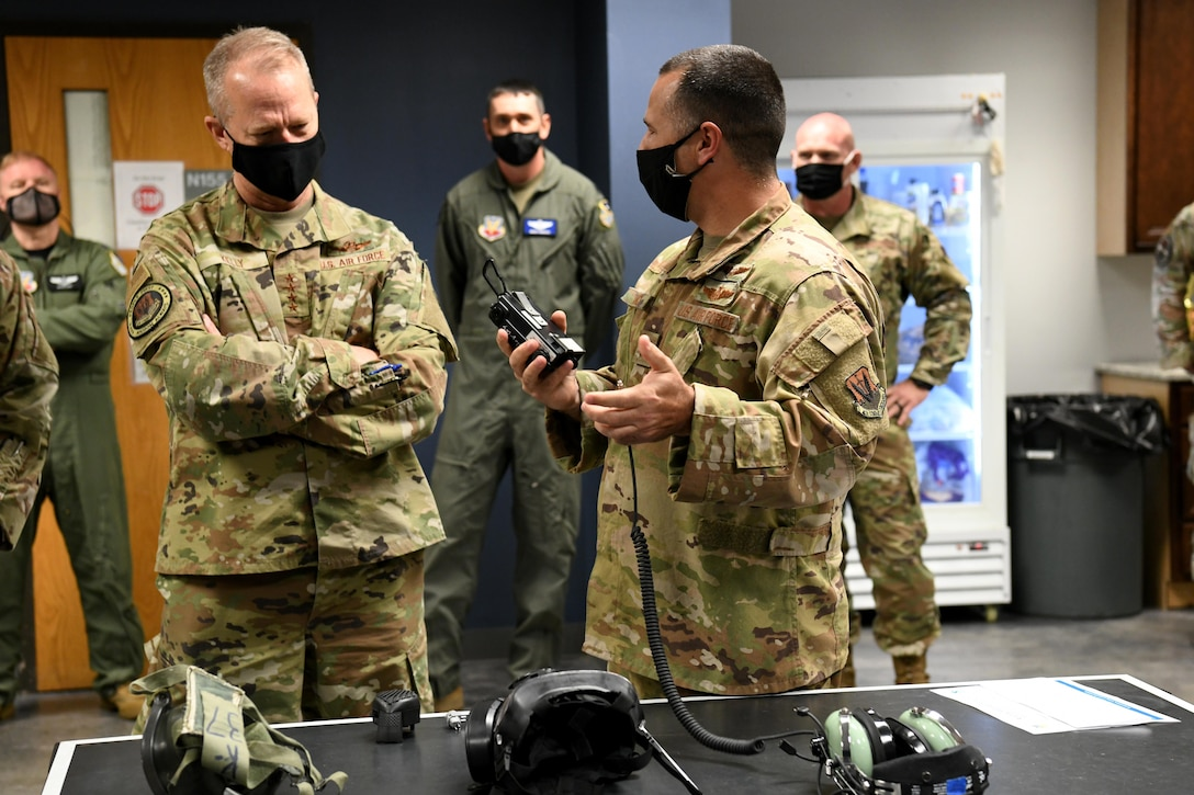 Photo shows group standing around equipment placed on table.