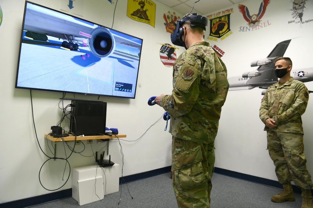 Photo shows general using VR helmet and hand remotes with an Airman standing by his side looking at a tv screen.
