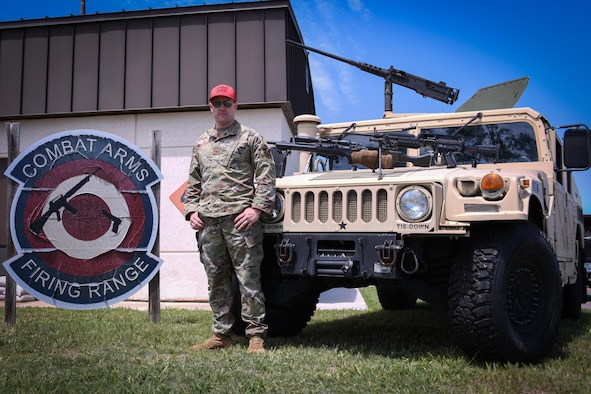 airmen poses in front of hummer