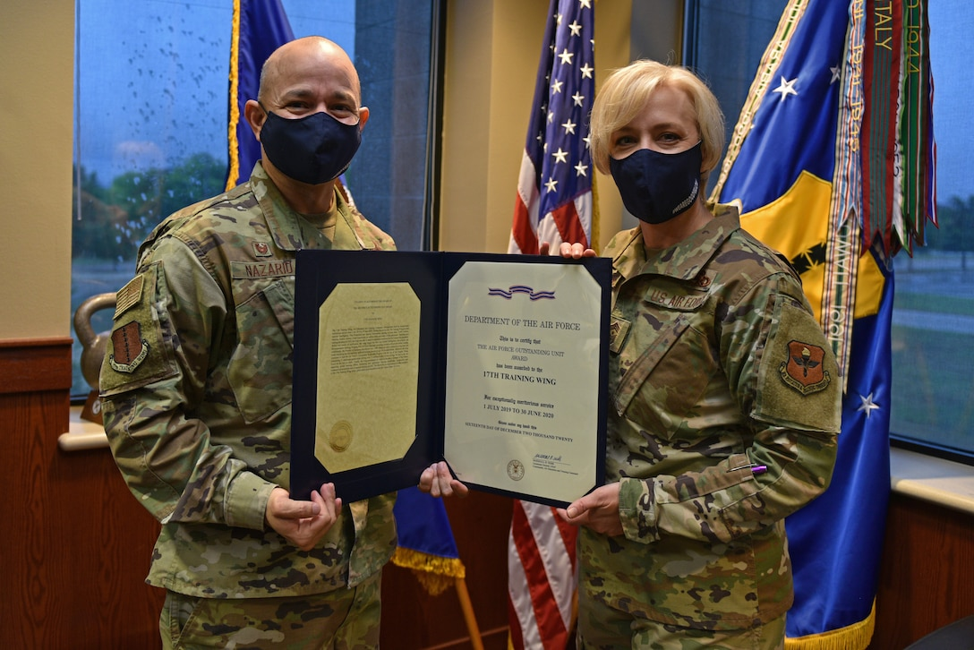 U.S. Air Force Col. Andres Nazario, 17th Training Wing commander, stands with Chief Master Sgt. Casy Boomershine, 17th TRW command chief, displaying the 2020 Air Force Outstanding Unit Award, in the Norma Brown Building on Goodfellow Air Force Base, Texas, May 11, 2021. The Outstanding Unit Award is awarded by the Secretary of the Air Force to units that have distinguished themselves through meritorious service or outstanding achievement. (U.S. Air Force photo by Senior Airman Ashley Thrash)