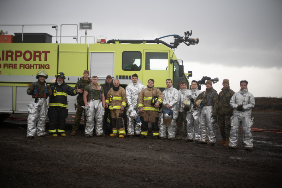 U.S. Marines and Sailors and Cold Bay Airport aircraft rescue firefighters pose for a photo in front of an Oshkosh Striker T3000 firetruck following a training event at Cold Bay Airport, Alaska in support of Northern Edge 2021.