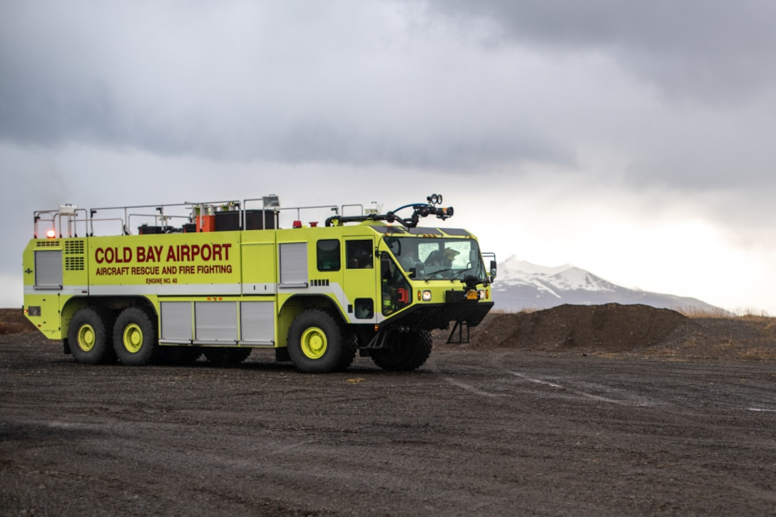 U.S. Marines and Cold Bay Airport rescue firefighters maneuver an Oshkosh Striker T3000 firetruck into position in preparation for a training event at Cold Bay airport, Alaska in support of Northern Edge 2021.