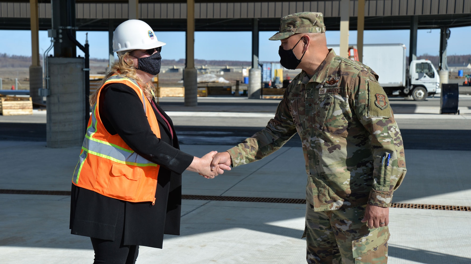 a military general officer shakes a woman's hand