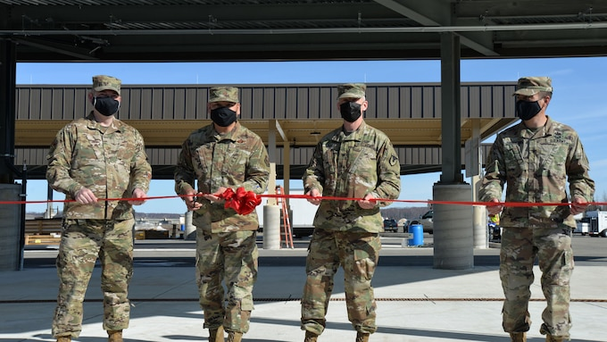 four military men stand to cut a ribbon