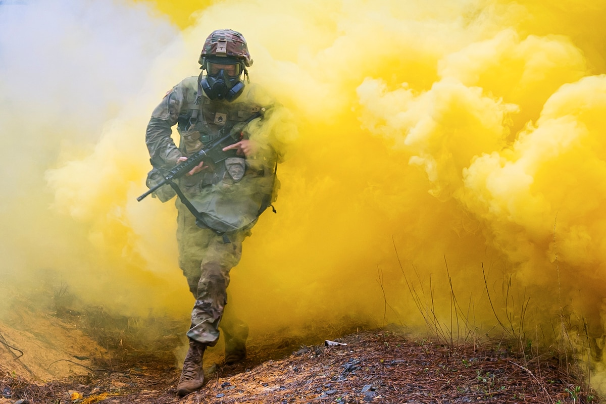 A soldier carrying a weapon runs through a cloud of yellow smoke.