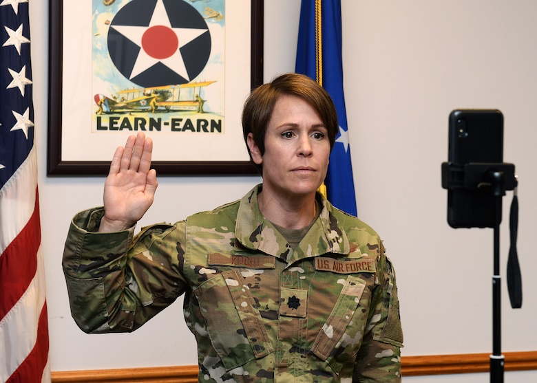 close up photograph of female lieutenant colonel in uniform with U.S. and Air Force flags behind her. Her right hand is raised as she stands in front of cell phone and verbally administers the oath of enlistment