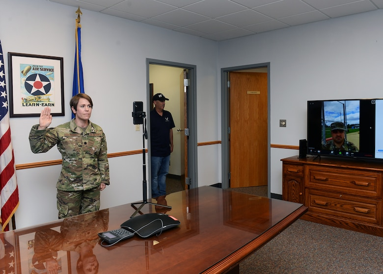 female Lieutenant Colonel standing in conference room with U.S. flag and Air Force flags behind her and in front of cell phone with her right hand raised to the right of the photograph a Technical Sergeant on a large television screen; as he takes oath of enlistment