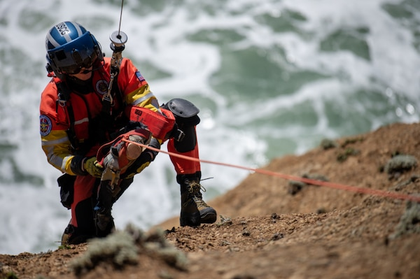 Petty Officer 2nd Class Noah Colburn, an aviation survival technician stationed at Air Station San Francisco, tends to a simulated individual during cliff rescue training Pacifica, Calif., March 30, 2021. Cliff rescue training is one of many exercise crews use to stay proficient in all mission capabilities. (U.S. Coast Guard Photo by Petty Officer 3rd Class Taylor Bacon)