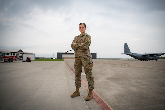 Airman stands on flight line in front of fire truck and C-130H Hercules