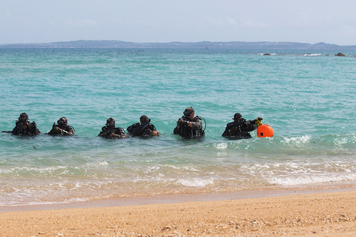 A line of six Marines move through water, one holding an orange item.