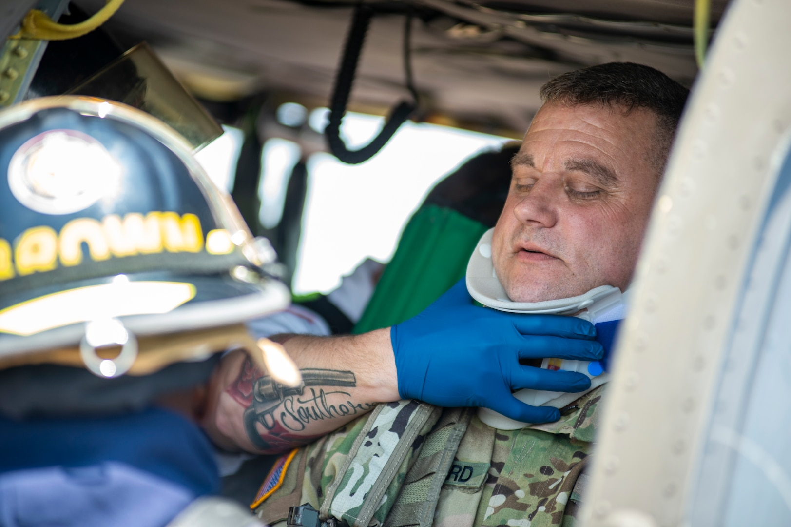 Fire fighters with the Tulsa, Oklahoma Fire Department and EMSA personnel place a neck brace on a mock casualty played by an Oklahoma Army National Guard Citizen-Soldier inside a simulated helicopter crash during pre-accident training at the Oklahoma Army National Guard's Army Aviation Support Facility 2 in Tulsa, Oklahoma, May 12, 2021. Pre-accident training prepares Army aviation units to respond to accidents ranging from slip and falls to mass casualty events. (Oklahoma National Guard photo by Anthony Jones)