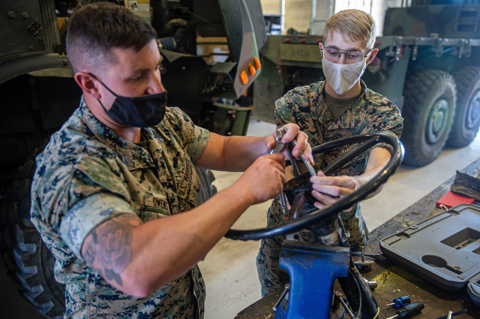 Cpl. Aiden Bemis,(right) a digital manufacturing engineer with 1st Supply Battalion, and Staff Sgt. Kyle Owens, (left) a motor transportation chief with Combat Logistics Battalion 5, demonstrate the old method of removing a steering wheel from the column using a 10-way slide hammer kit.