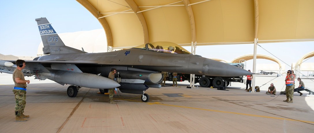 """Members of the 379th Expeditionary Maintenance Squadron perform a """"hot pit"""" refueling under the supervision of 378th Expeditionary Operations Group training instructors, Prince Sultan Air Base, Kingdom of Saudi Arabia, May 3, 2021. Hot pit refueling is where maintainers refuel an aircraft while the engine is still running, allowing the aircraft to safely and quickly return to flying. (U.S. Air Force Photo by Senior Airman Samuel Earick)"""