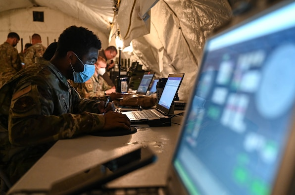 Airmen use laptops in a makeshift forward operating base during the Agile Flag 21-2 exercise at Naval Outlying Landing Field Choctaw, Fla., May 3, 2021. Air Combat Command developed the Agile Flag 21-2 experiment to create a lead wing, aligning squadrons from different locations under a single commander, enhancing their readiness as a team before deploying into a contested environment.