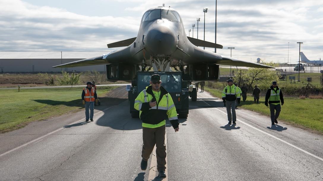 B-1B aircraft being towed down road.
