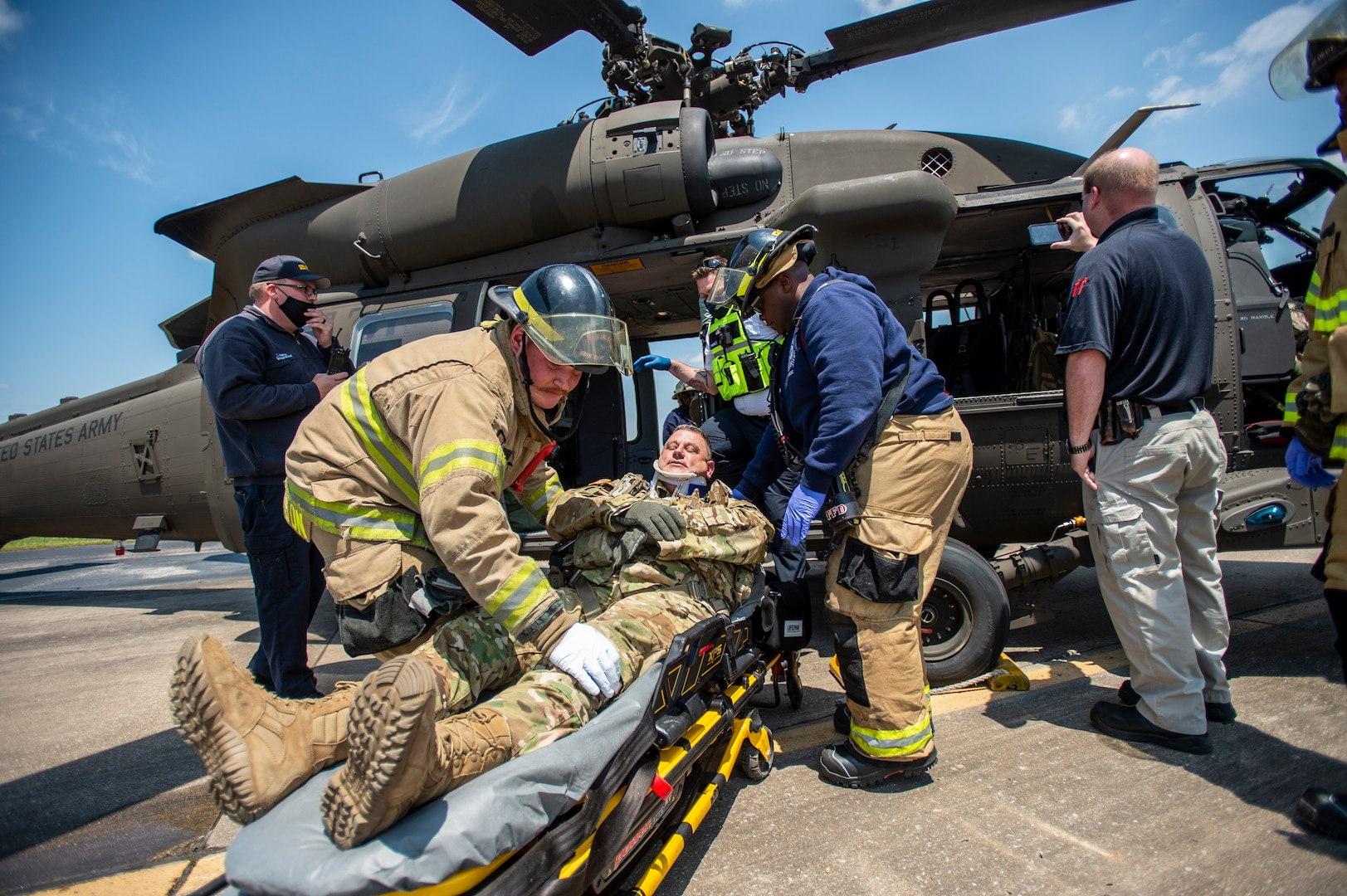 Firefighters and other first responders extract a simulated casualty played by an Oklahoma Army National Guard Citizen-Soldier from a mock helicopter crash during training at the Guard's Army Aviation Support Facility 2 in Tulsa, Oklahoma, May 12, 2021. The training prepares Army aviation units to respond to accidents ranging from slip and falls to mass casualty events.
