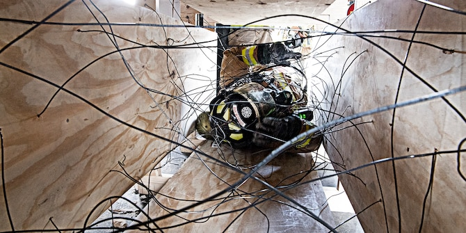 Firefighters attending the rescue and survival course at Grissom May 10-14 had to work their way through an entrapment exercise wearing their bunker gear. Firefighters from six different departments gathered here for an intense week of training. (Air Force photo by Douglas Hays)