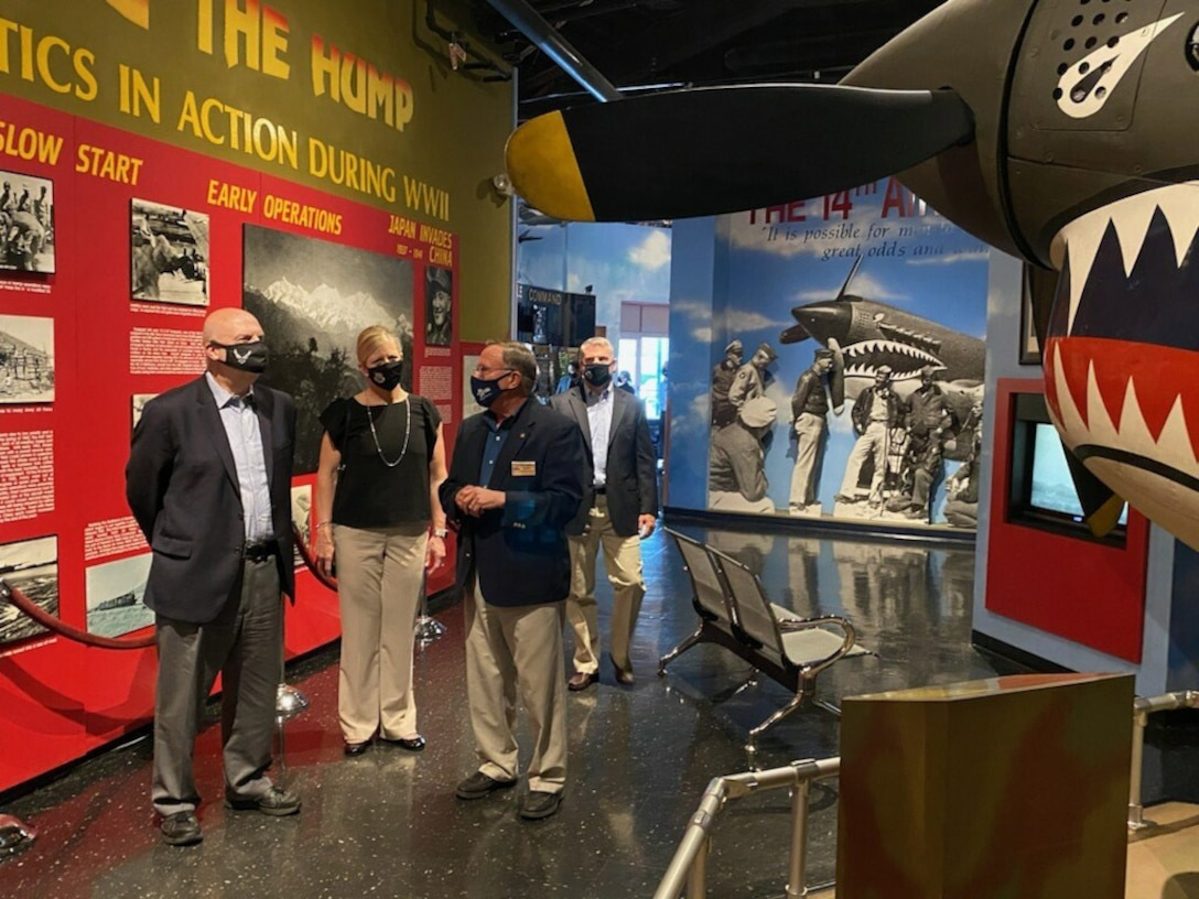 Photo shows group standing in front of an indoor airplane exhibit.