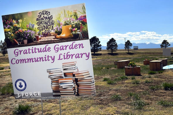 A photo of the Schriever community garden and library sign