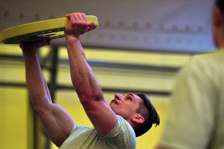 Member completes an overhead press with a 35 pound weight