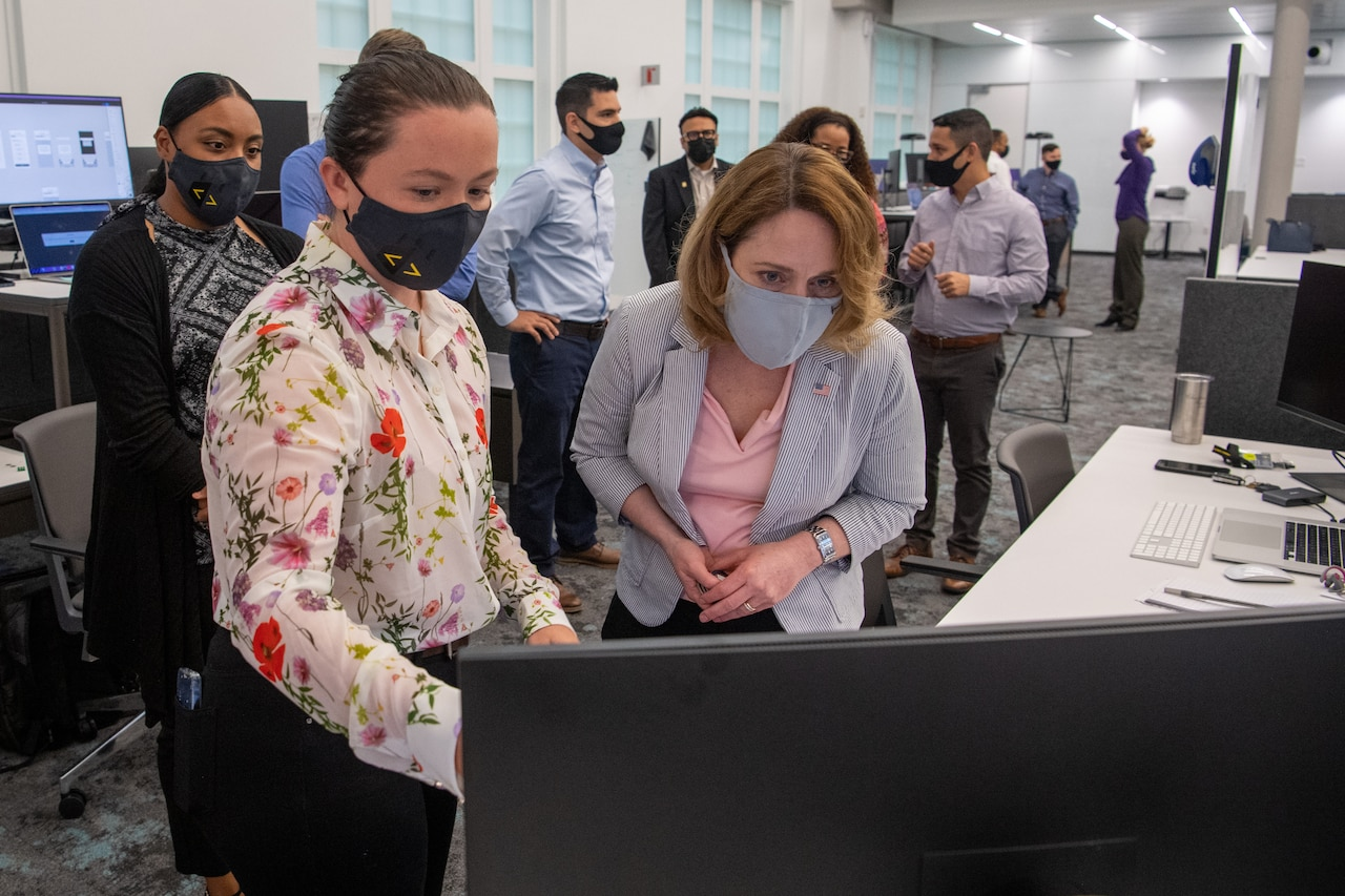 Two women look at a computer monitor in an office as others watch from behind.