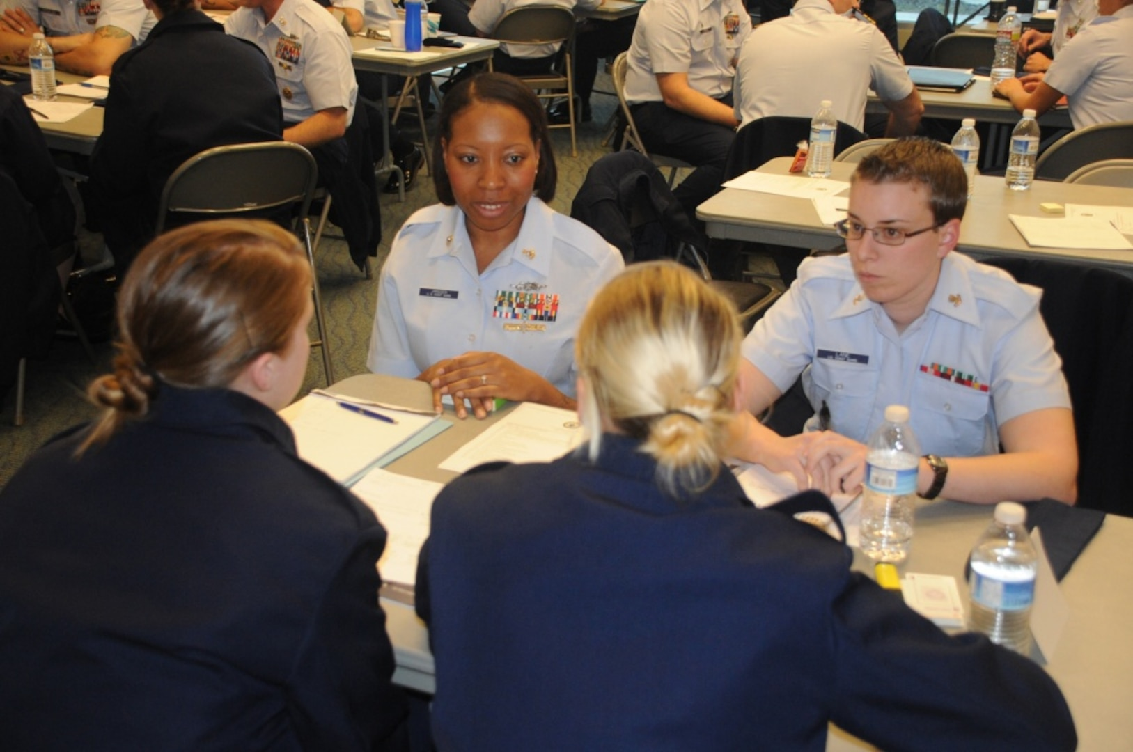 """Chief Petty Officer, Rekiya Janssen (top left) of the Naval Engineering Support Unit Maintenance Augmentation Team in Alameda, Calif., speaks with attendees of the """"Women in D13"""" workshop at the Columbia River Maritime Museum, Dec. 12, 2012, during a speed mentoring session. Guests to the event had a chance to meet with and learn from female Coast Guard members in senior leadership positions during the two-day workshop. Coast Guard photo by Petty Officer Shawn Eggert"""