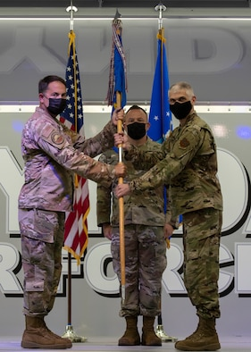 U.S. Air Force Col. Greg Moseley, 325th Fighter Wing commander, left, passes the guidon  to Col. Steven Collen, 325th Maintenance Group commander, right, during an assumption of command ceremony at Tyndall Air Force Base, Florida, May 11, 2021.