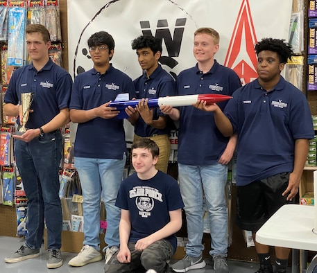 Picture of six young men holding a model rocket and a trophy