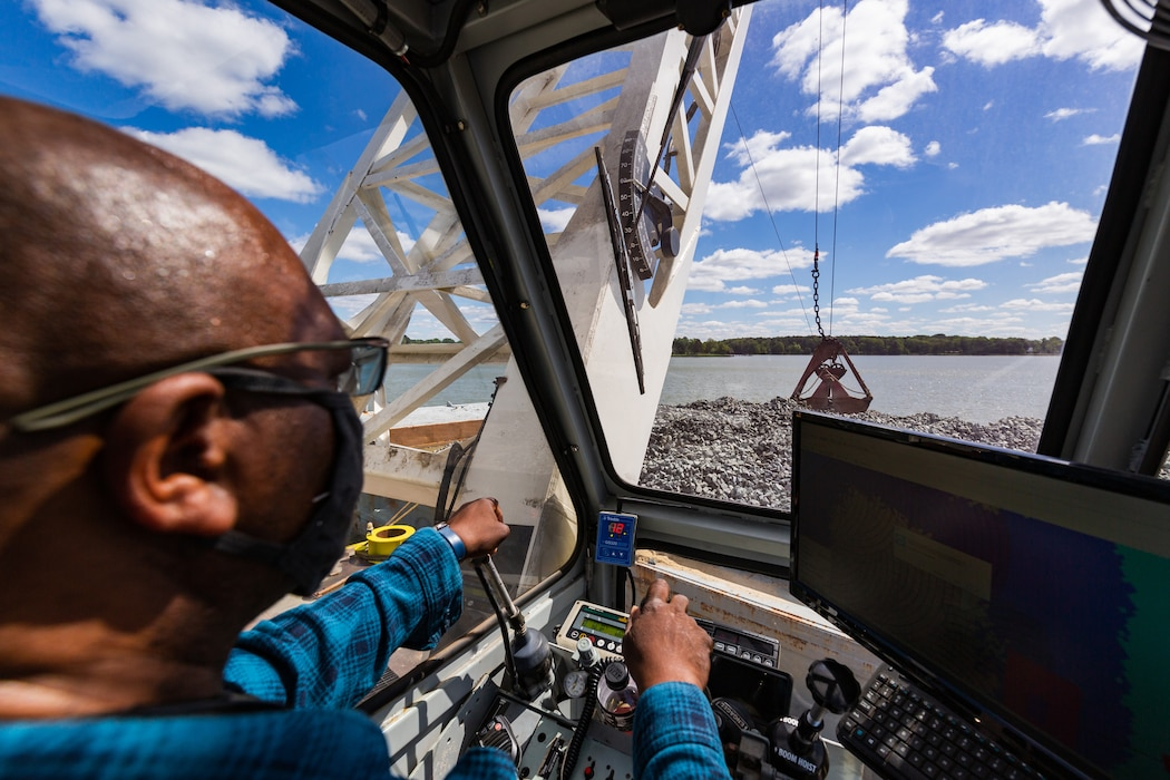 Clarence Hinton, a crane operator, maneuvers  picks up rock to place in the Tred Avon River Oyster Sanctuary in Talbot County, Maryland May 6, 2021. The U.S. Army Corps of Engineers, Baltimore District, along with federal and non-federal partners resumed construction of the oyster reefs in April and approximately 34 acres of reef will be restored when the work is completed. (USACE photo by Christopher