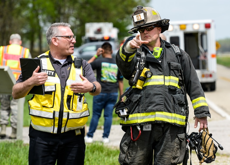 A firefighter from the 788th Civil Engineer Fire Department, talks with an individual from the 88th Air Base Wing safety office during a base exercise at Huffman Prairie Flying Field, Wright-Patterson Air Force Base, Ohio, May 2, 2019. (U.S. Air Force photo by Wesley Farnsworth)