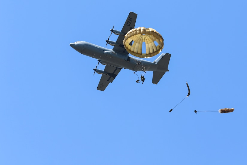 Soldiers parachute from a C-130 airplane.