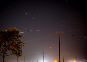 Starlink satellites fly by in space above Edwards Air Force Base, California, May 7. (Air Force photo by Giancarlo Casem)