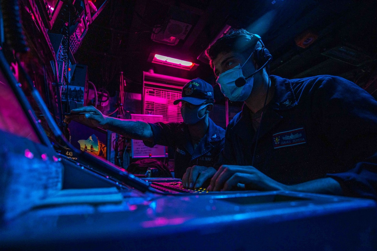 Two sailors monitor a board on a ship lit in blue and pink lights.