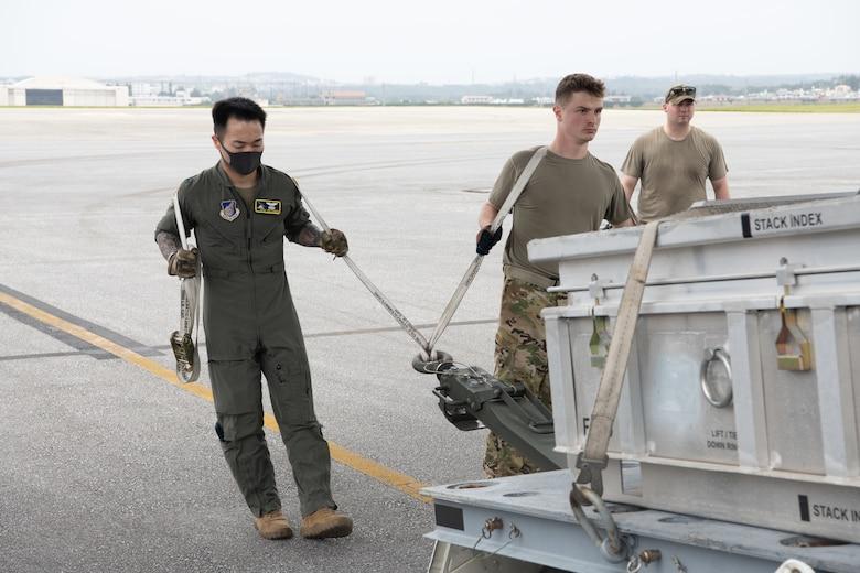 Airmen lifting munitions crate into aircraft