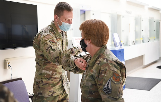 Air Force Surgeon General Lt. Gen. Dorothy Hogg bumps elbows with Capt. Scott Coberly, 66th Medical squadron pharmacist, after presenting him a coin at Hanscom Air Force Base, Mass., May 11. During her visit to the 66 MDS clinic, Hogg coined four star performers for their efforts throughout COVID-19. (U.S. Air Force photo by Lauren Russell)