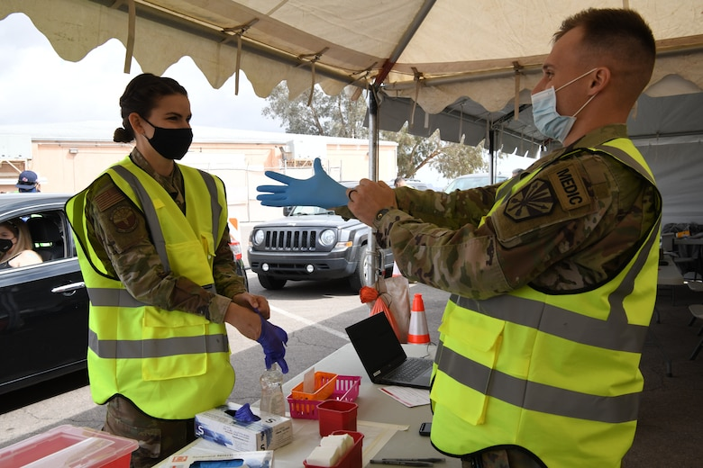 Reserve Airman Senior Airman Danielle Ippolito, 944th Medical Squadron nurse, and Army Guard Specialist Karston Gardner, Combat Medic, 856th Military Police Company, prepare to administer COVID-19 shots to Salt River Pima-Maricopa Indian Community residents at the Salt-River Point of Dispensing site, March 26, 2021. As part of the Arizona National Guard Task Force Medical, servicemembers are augmenting vaccination sites for communities with low staffing and a high demand.