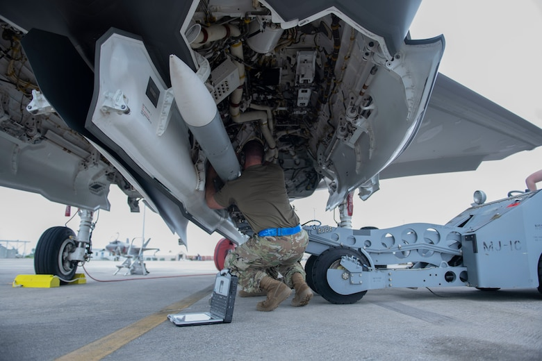 Man loading a missile onto an aircraft