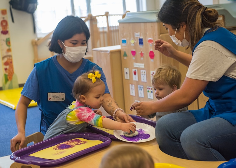 Yoiko Child Development Center teachers assist students during a stamp painting activity at Misawa Air Base, Japan, April 26, 2021.