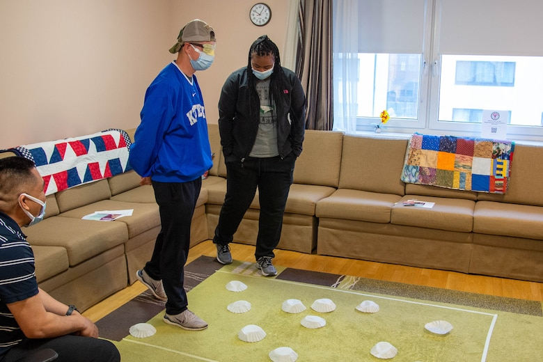 A woman guides a blindfolded man across a carpet with coffee filters on it.
