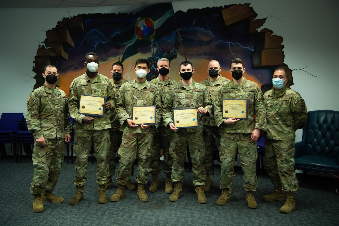 Airmen hold graduation certificates