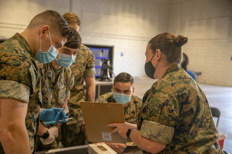 U.S. Navy Lt. Rebecca Gerena, from 2d Marine Division base out of Camp Lejeune, North Carolina, explains procedures to Navy Corpsman at the Memphis Community Vaccination Center in Memphis, Tennessee, May 12, 2021. U.S. Northern Command, through U.S. Army North, remains committed to providing continued flexible Department of Defense support to the Federal Emergency Management Agency as part of the whole-of-government response to COVID-19. (U.S. Marine Corps photo by LCpl. Justin T Brown/2dMARDIV)