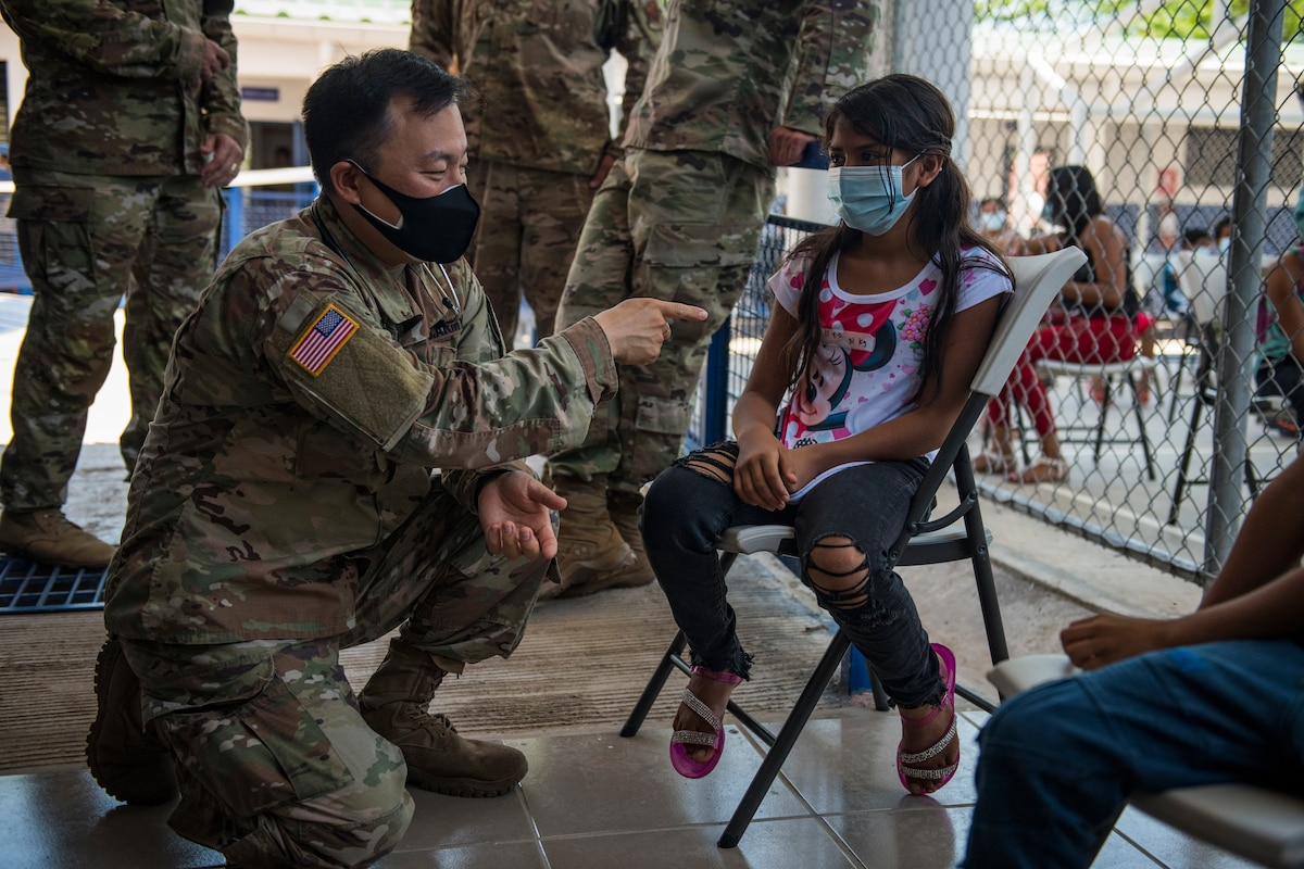 A soldier kneels as he speaks to a young woman sitting in a chair.