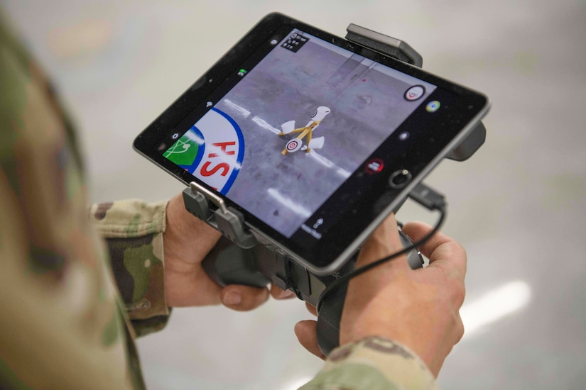 A service member operates a hand-held electronic device.