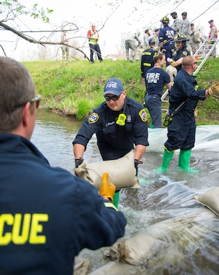 Tim Howells, 788th Civil Engineering Fire Department, passes a sandbag on as part of an assembly line helping to build a dam in Hebble Creek May 2, 2018, on Wright-Patterson Air Force Base, Ohio. The project was part of a base exercise used to train personnel in emergency response. In this case, a simulated fuel spill. (U.S. Air Force photo by R.J. Oriez)