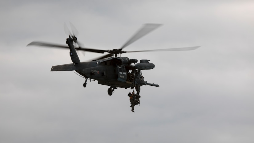 A helicopter hoists a Marine by a rope.