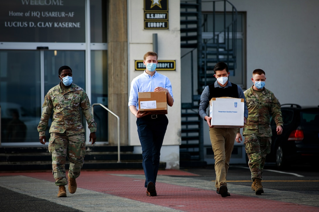 Four men, civilian and military, wear face masks as they carry boxes outside a building.